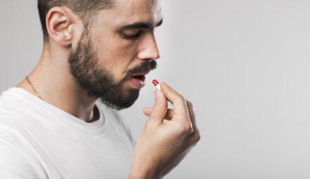 homem tomando medicamentos