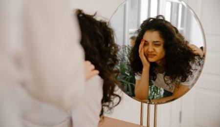 mulher com autoestima baixa se olhando no espelho