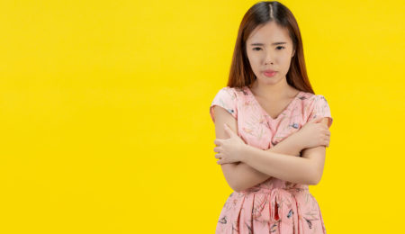 Mulher se abraçando em fundo amarelo - baixa autoestima