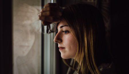 mulher com medo e ansiedade olhando pelo janela