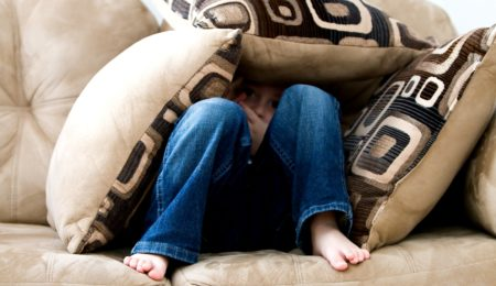 criança escondida atrás de almofadas no sofá - fobia