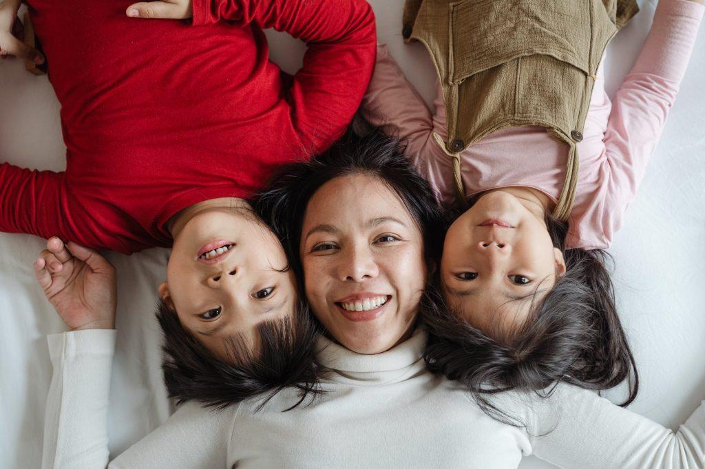 mãe e duas filhas meninas crianças deitadas na cama causas de autismo